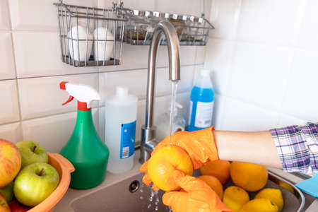Washing fresh fruits in the kitchen under cold running tap water