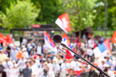 Political protest or public demonstration, focus on microphone, blurred crowd of people holding flags in the background 免版税图像