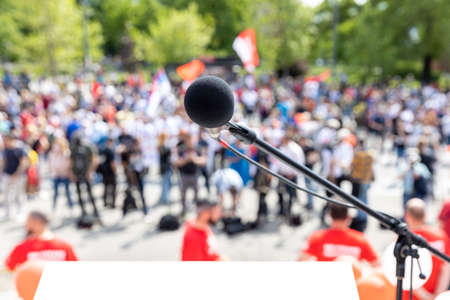 Political protest, meeting or demonstration, focus on microphone, blurred crowd of people in the background