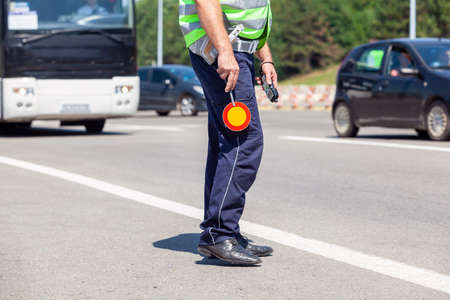 Police officer controlling traffic on the highway, bus and cars in the background