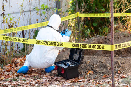 Crime scene investigation. Forensic science specialist photographing human remains. 免版税图像