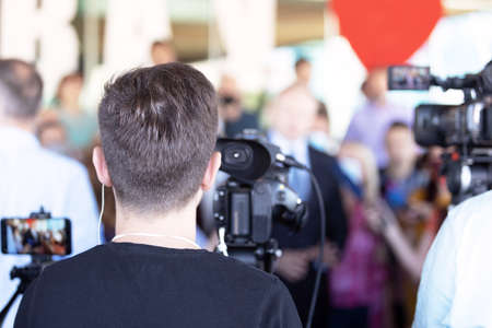 Cameraman filming media event or news conference with a video camera 免版税图像