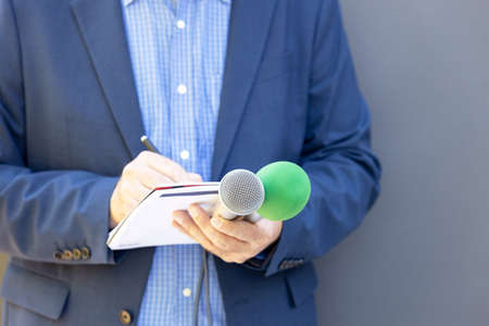 Journalist at news conference or media event, holding microphone, writing notes. Broadcast journalism concept.