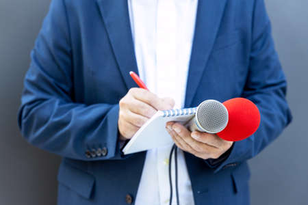 Journalist at media event or press conference, holding microphone, writing notes. Broadcast journalism concept. 免版税图像