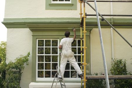 ladder safety: Painter decorating a house exterior.