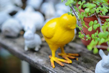 Yellow Chickhen statues in the green garden.