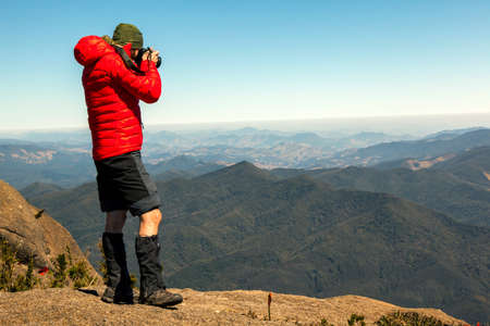 Mountaineer photographer in rock mountain summit