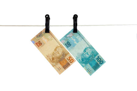 Brazilian Real bank notes in a clothesline - Money laundering - dirty money concept - isolated in white background