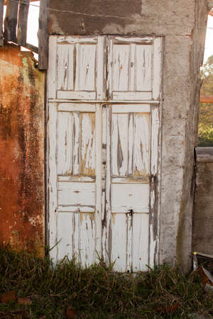 Old white colored door in abandoned house in countryside Imagens