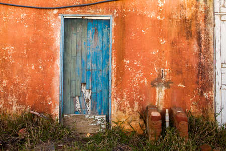 Old blue colored door in abandoned house in countryside Imagens
