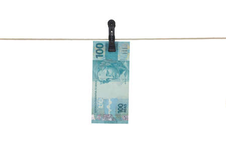 Brazilian 100 Real bank note in a clothesline - Money laundering - dirty money  concept - isolated in white background Reklamní fotografie