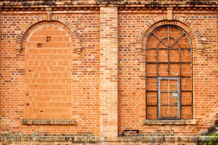 Closed windows in old orange brick wall