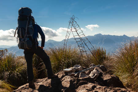 Unrecognized people with great backpacks enjoying the mountain landscape view from a mountain summit Stock Photo