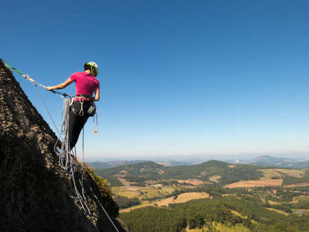 Woman rock climber in a steep rock with beautiful landscape in the background