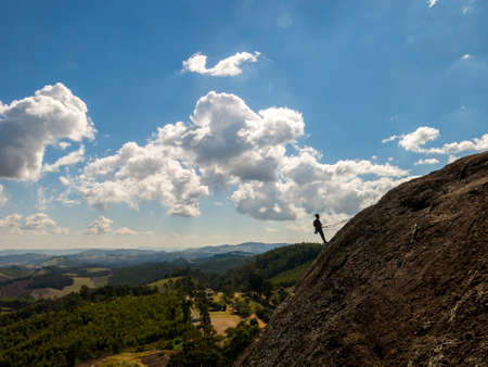 Rock climber silhouette in a steep rock with beautiful landscape in the background