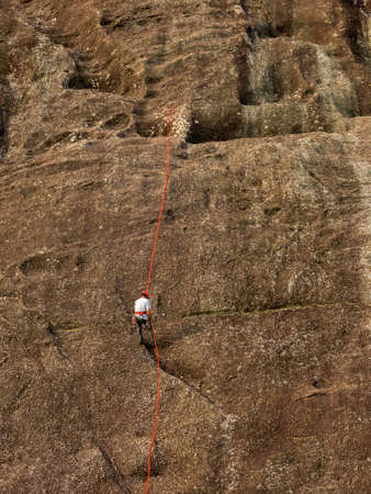 People abseiling a steep rock mountain wall