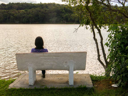 Unrecognized girl sitted in a seat in front of a lake in backlight