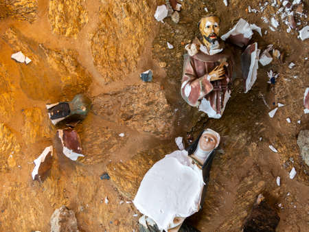 Broken vandalized plaster catholic plaster statues in the ground