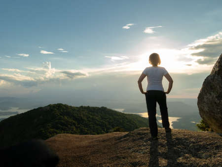 Unrecognized people - girl in mountain summit top looking landscape and dam reservoir - backlight sunset