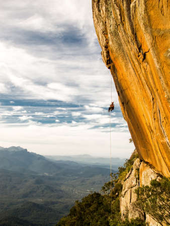 Abseiling a negative yellow rock wall with mountains on background