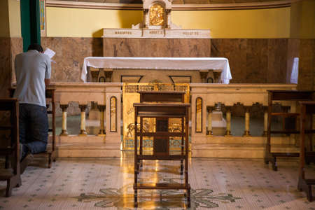 Man praying in a baroque church