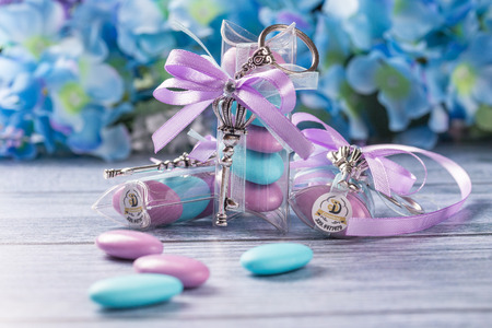 Wedding favors. Boxes with purple and white ribbon containing violet and blue confetti and key gift.