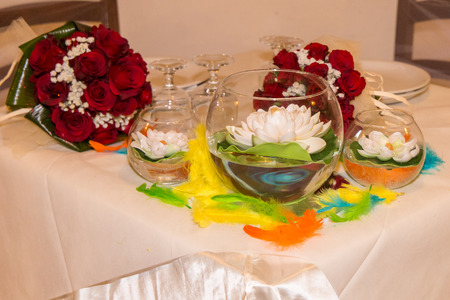 christian marriage: Rainbow wedding or event production. Two red roses and two bowl with lotus flowers Stock Photo