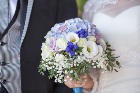 A floral wedding bouquet in bride's hands