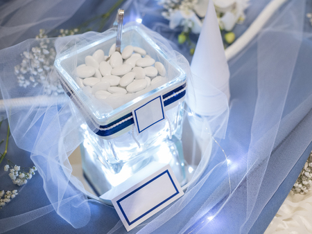 Lighted jar with confetti with white label to personalize image, rope for decoration and cone for confetti on blue table.