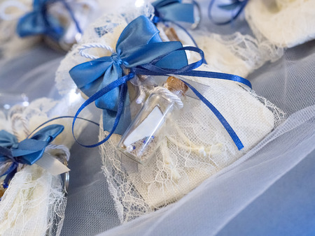 Wedding favor decorated with lace and blue ribbon with message in a bottle with white labels ready to personalize with your text Stockfoto