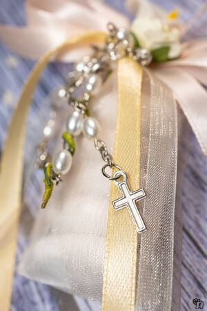 Wedding favors. Boxes with pink and gold ribbon containing  confetti and tiny christian rosary gift.