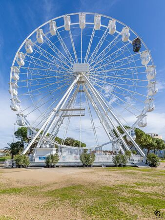 Ferris wheel in in front of the sea in Olbia center park surrounded by palm trees and near the museum of the city