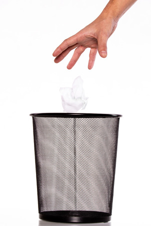 wastebasket: Hand throw a paper into Metal trash bin Stock Photo