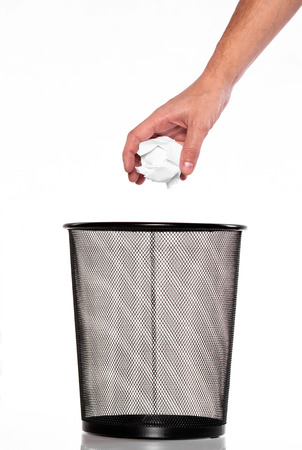Hand throw a paper into Metal trash bin Stock Photo