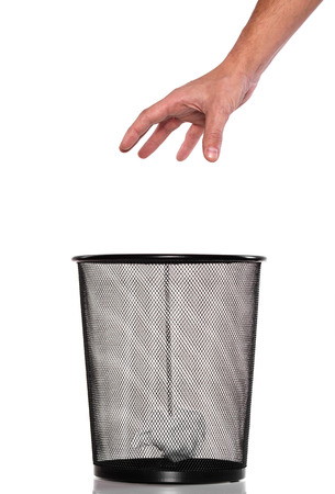 Hand throw a paper into Metal trash bin photo
