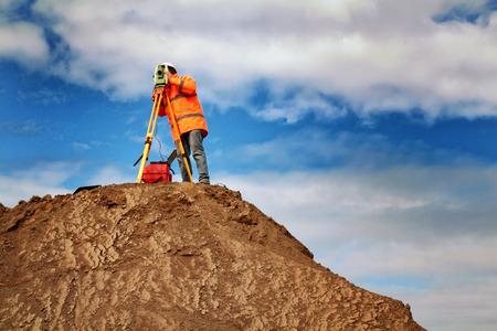 land surveyor on mound 스톡 콘텐츠