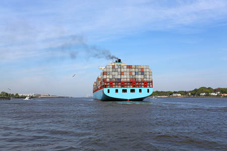 blue containership on river elbe Foto de archivo