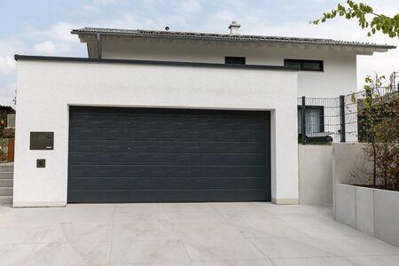Black garage door in white building Stockfoto