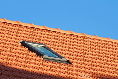 Small skylight on red rooftop Foto de archivo