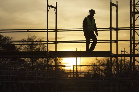 Silhouette of a worker on scaffolding at sunset