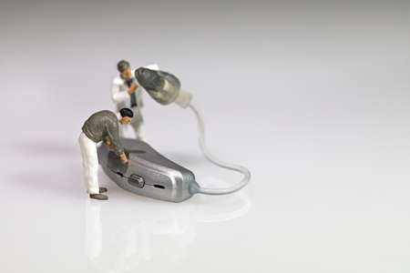 miniature figures doing hearing aid maintenance