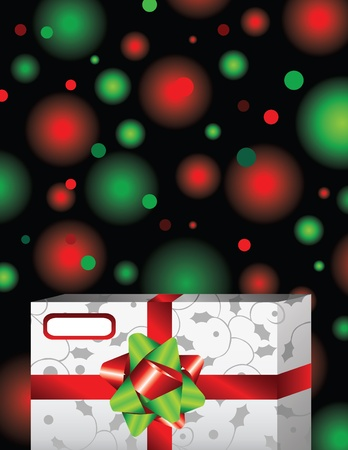 A decorative holiday gift in front of a Christmas tree of red and green lights