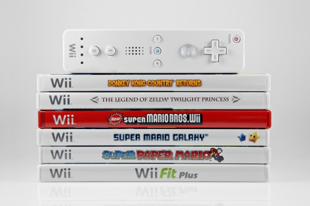 nintendo: Springfield, Missouri - March 17, 2011: A studio shot of a stack of 6 Nintendo Wii video games and controller.