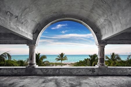 arcos de piedra: Una hermosa vista del océano desde el interior de una vieja mansión abandonada. Foto de archivo