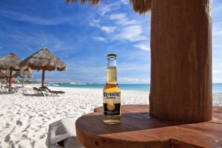 Cancun, Mexico - September 29, 2011: A bottle of Corona (labeled as Coronita in Mexico) under a palapa on Maroma Beach.