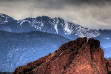 A close up shot of one of the large red rocks at garden of the gods park in Colorado with snowcapped mountains in the background. Foto de archivo