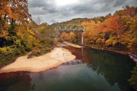 A bridge over the Buffalo River in Arkansas shot in the peak of the Fall season