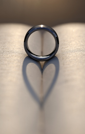 Wedding ring between the pages of an old book with the sunlight casting a heart shaped shadow