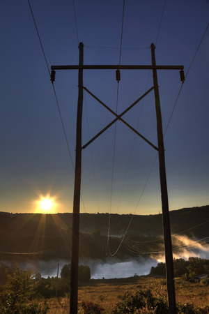 Power lines crossing at lake at sunrise