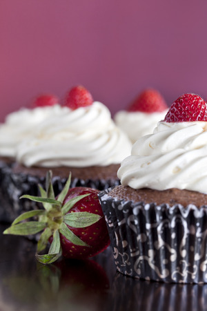 Chocolate cupcakes with vanilla icing topped with strawberries Foto de archivo